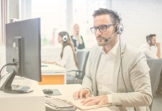 Employee using communication and productivity to help a customer via a desktop and headset