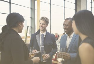 Businesspeople discussing products with drinks in hand — leverage existing customers