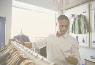 Person shopping in clothing store and looking at smartphone — UC customer experience integration
