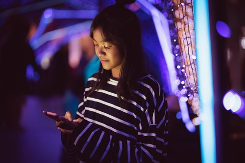 Asian young girl using a mobile phone in downtown, Bokeh city light in background