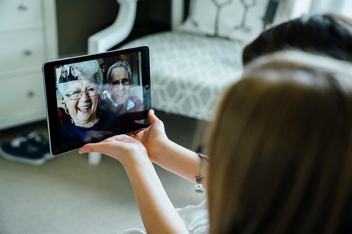 Sisters video conferencing with grandparents through tablet computer at home