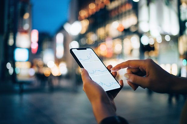 Businesswoman reading financial trading data on smartphone in downtown city street against illuminated urban skyscrapers