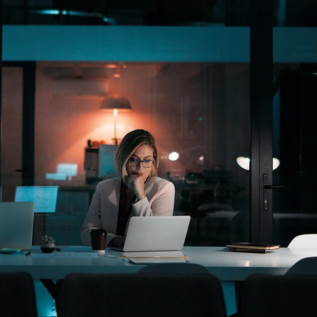 Shot of a businesswoman using a laptop at her desk during a late night at work
