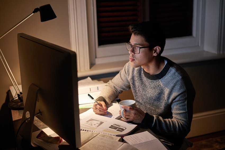 A male student sitting at a desk taking a class from home on his computer