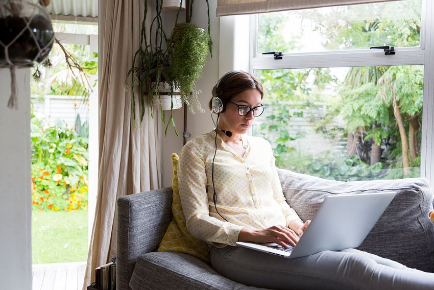 Woman sitting on her coach at home working from her laptop with headset on