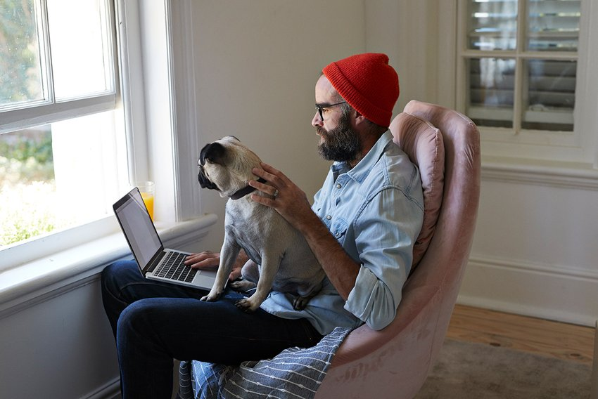 Man working from home with his dog on his lap while on his laptop