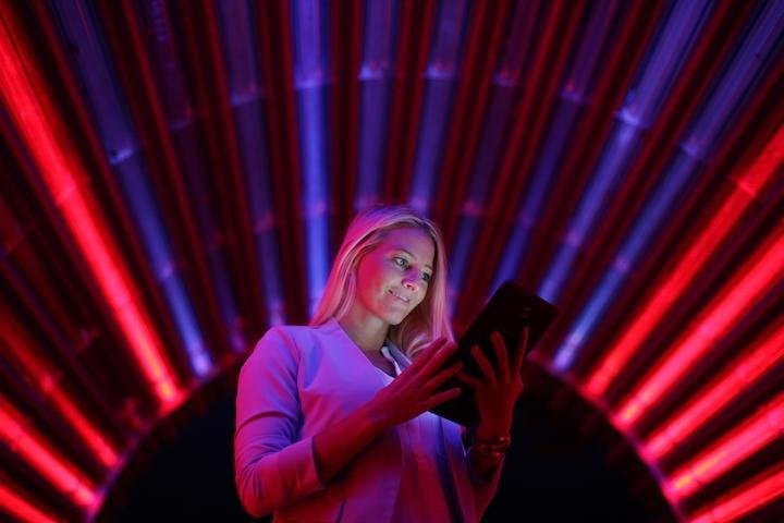 Woman on tablet in dark room with red lights