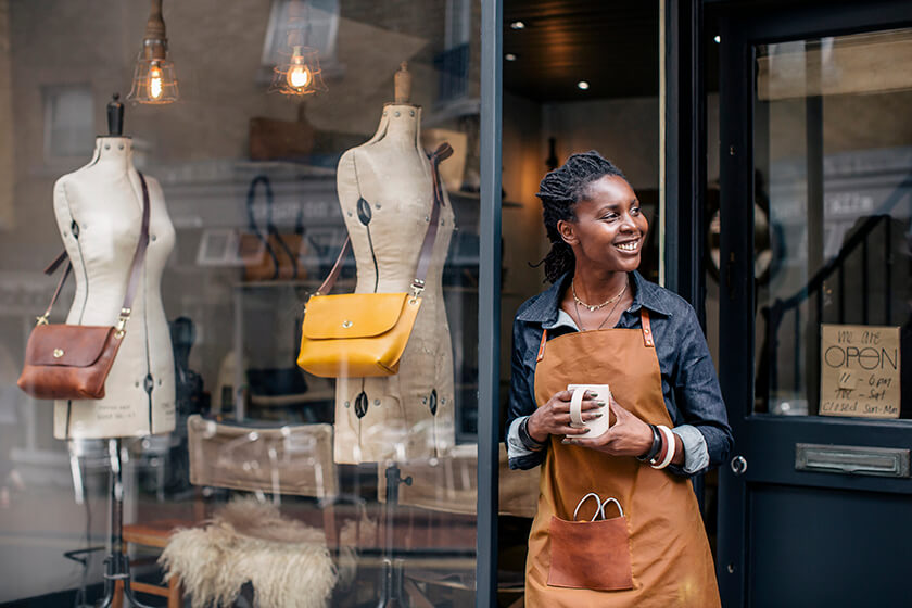 business owner standing outside fashion shop holding cup of coffee